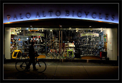 Palo Alto Bicycles  A passing bicyclist can't resist the alluring window display at night.  Palo Alto, California  27-AUG-2011