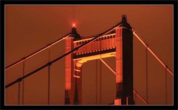 "Sodium & International Orange  During the night, sodium lamps cast an orange glow on the ""international orange"" Golden Gate Bridge and surrounding clouds.  San Francisco, California  11-JUN-2011"