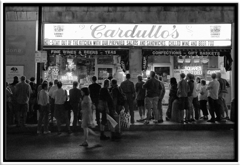 Red Sox After Hours  On a very hot evening, Red Sox fans stop and gather around a TV in the display window of (a closed) Cardullo's, a long-time landmark sandwich shop & store in Harvard Square.  Harvard Square Cambridge, Massachusetts  05-AUG-2006