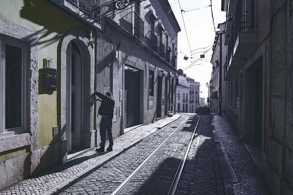 Man works in the street outside a building in Lisbon, Portugal