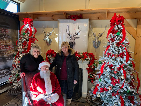 . Santa and helpers, Nordblom Property Manager (aka, the Mayor of 3rd Ave.) Molly Bennett, left, and her mom, Mary Bennett, both of Chelmsford