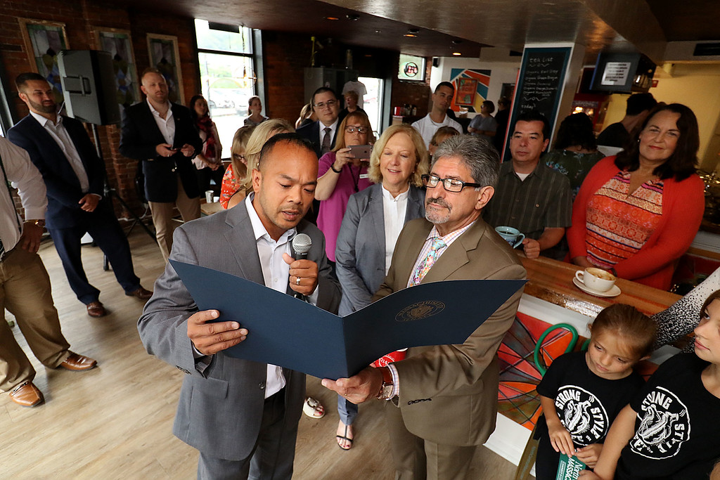 ". The new ""Strong Style Coffee\"" shop in Fitchburg held a ribbon cutting on Thursday, September 13, 2018. State Senator Dean Tran reads a citation from the State Senate, with a little help from Fitchburg Mayor Stephen DiNatale, for the new coffee shop after they cut the ribbon. SENTINEL & ENTERPRISE/JOHN LOVE"