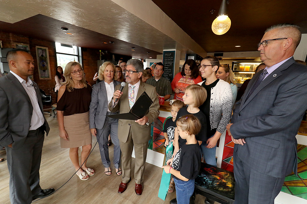 ". The new ""Strong Style Coffee\"" shop in Fitchburg held a ribbon cutting on Thursday, September 13, 2018. Mayor Stephen DiNatale reads a citation from the city to the coffee shop after they cut the ribbon. SENTINEL & ENTERPRISE/JOHN LOVE"