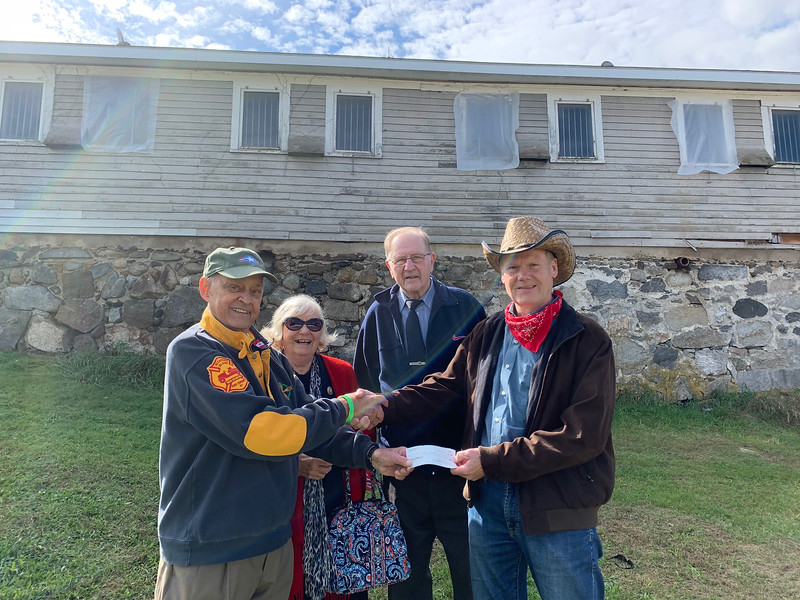 The group Forget Them Not, represented by, from left, founder Robert Page, Ann Marie Page and Roland Provencher, all of Lowell, present a donation to Strongwater Farm board Vice President Chris Perley of Tewksbury.
