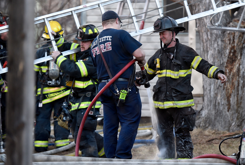 . A firefighters has his gear rinsed off after working to put out a structure fire on Modred Street on Wednesday in Lafayette. For more photos of the firefighters working the scene go to www.dailycamera.com Jeremy Papasso/ Staff Photographer/ Feb. 15, 2017