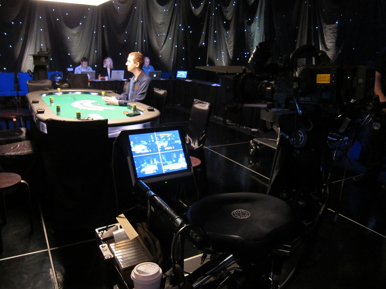 "I see my seat there, to the left of the dealer.  The T.V. table includes ""pocket cams"" in front of which players expose their cards.  This super-secret footage is then spliced into the time delayed broadcast."