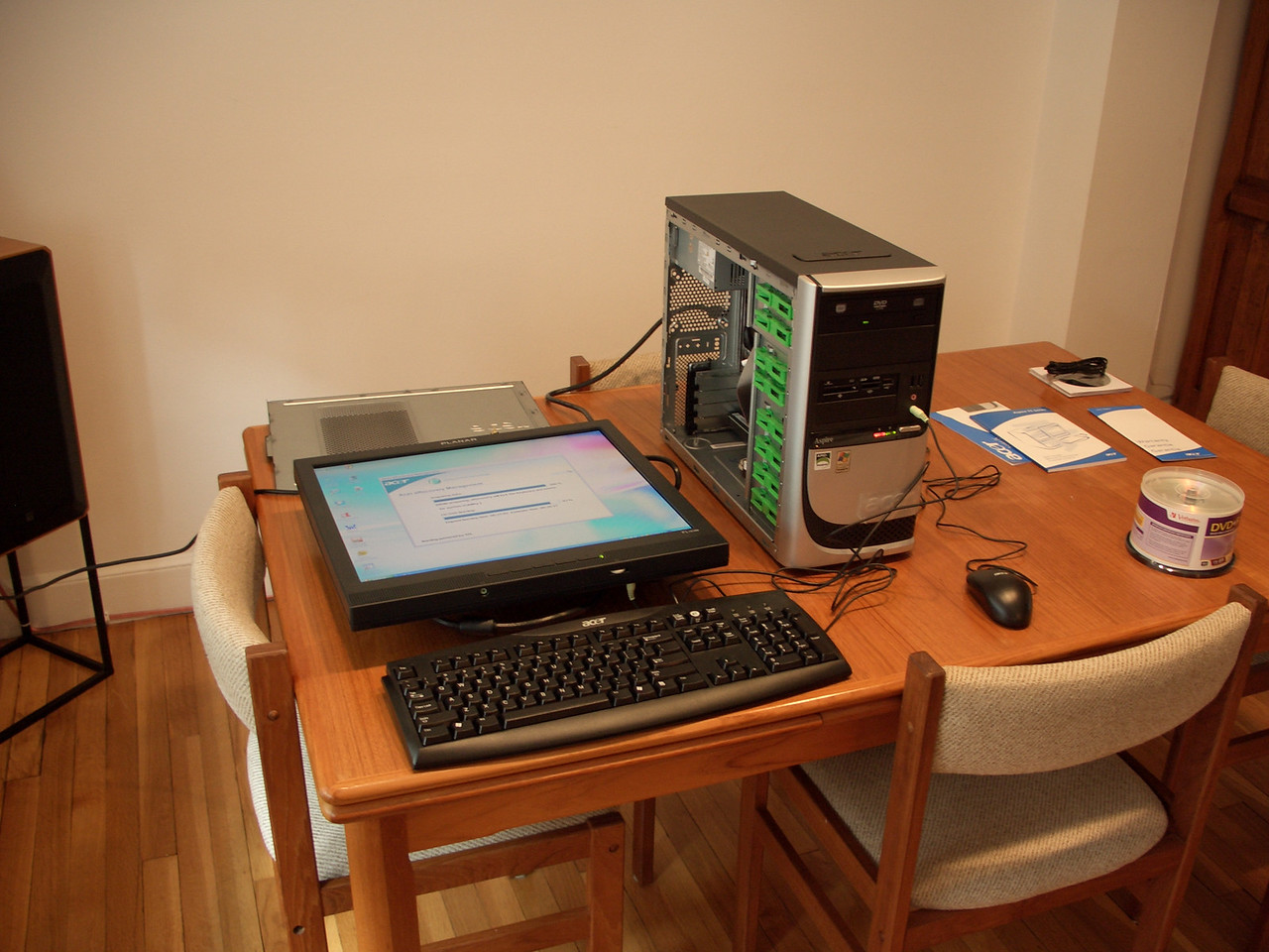 I forked out about $350 bucks for a low end ACER PC.  There were many considerations here.  I wasn't too concerned about computational horsepower as I figured the box would be used mostly for slide shows, watching video, and web browsing.  <br /> <br /> Noise was a concern.  It's a nice coincidence that slow PC's generate less heat, have smaller power supplies, and correspondingly tiny, quiet, fans.  I went to several local stores just to put my ear on the cases of potential models (only drew a few odd looks).  <br /> <br /> This pick comes with 512MB RAM, DVD burner, plenty of USB 2.0 ports, on-board audio/video.  I removed the modem card that was included.  I also got rid of the mouse and keyboard, but more on that in a minute.