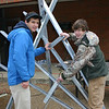 Two students assemble a sculpture.
