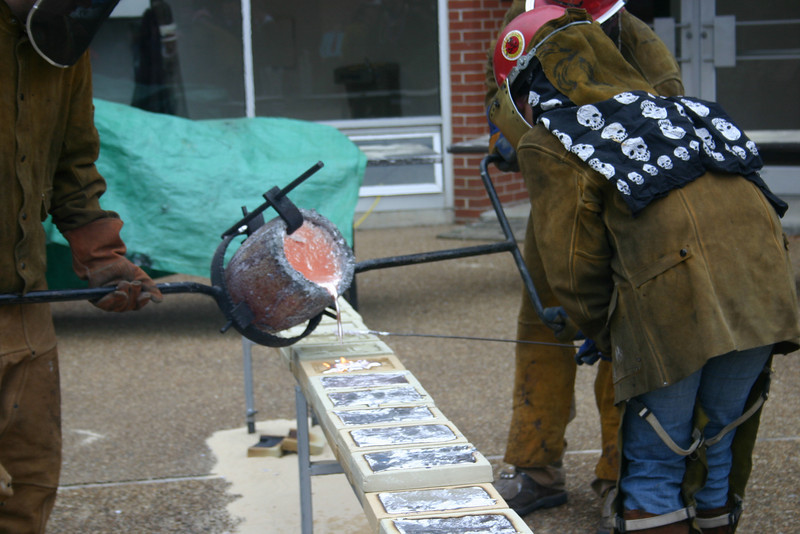 The sculptor team pours hot metal into molds prepared by students and faculty.