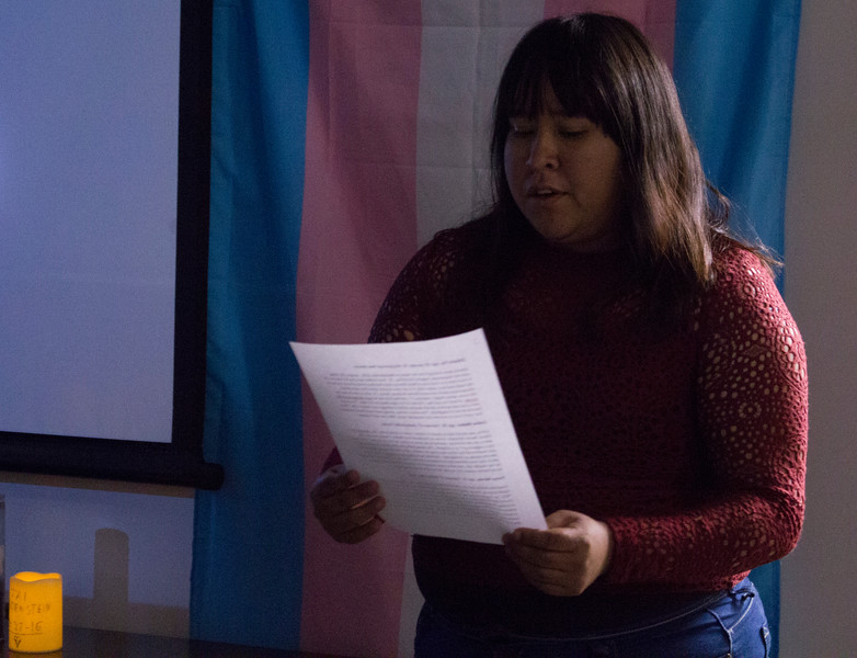 A student from the Sexuality and Gender Awareness club reads a description about a transgender person who was murdered.