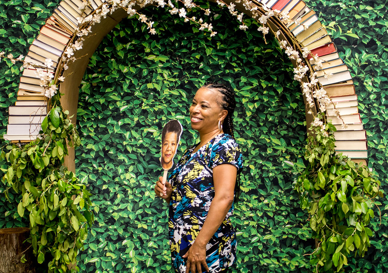 An English Meet and Greet participant poses in front of the photo booth area with a cutout of Maya Angelou.