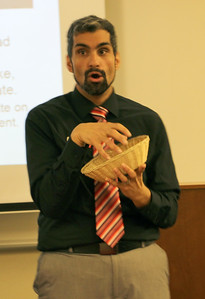 Nicky Damania shows students how to pass the bread.