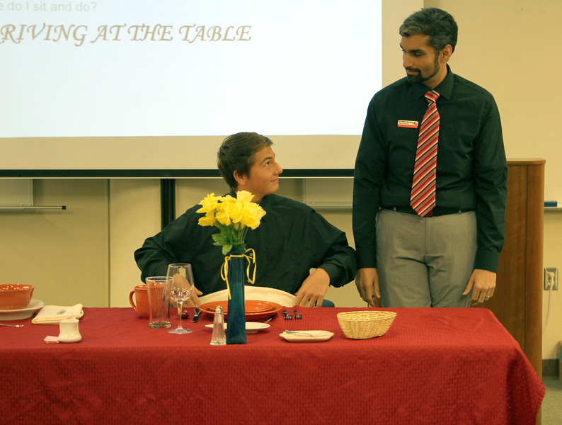 Dr. Nicky Damania demonstrates table etiquette with a student in the Levan Center.