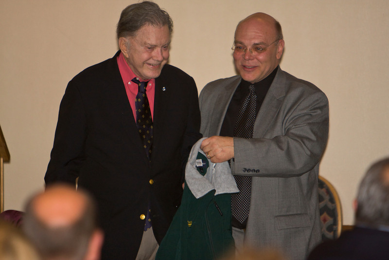 RMC President Michael Mace presents an RMC flight jacket to Cliff Robertson, actor and aviator, who is this year's commencement speaker.