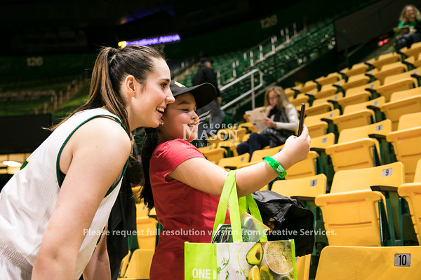 Natalie Butler signs autographs for elementary school kids visiting during the George Mason University women's basketball game against the University of Richmond.  Photo by:  Ron Aira/Creative Services/George Mason University