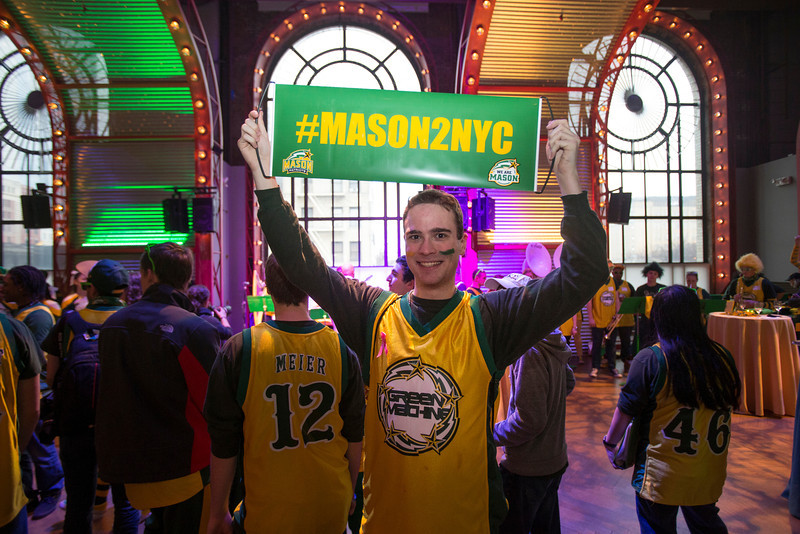 "A member of the Green Machine holds up a ""#mason2nyc"" banner during the Ignite Your Mason Spirit Reception at the Brooklyn Academy of Music - Lepercq Space in Brooklyn, NY. George Mason Patriots play against the Fordham Rams in the Opening Round of the 2014 Atlantic 10 Men's Basketball Championship. Photo by Craig Bisacre/Creative Services/George Mason University"