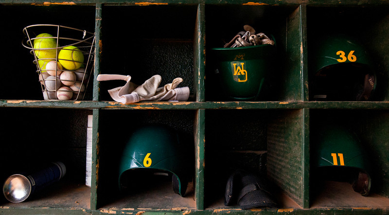 Baseball gear belonging to Mason's Mens Baseball team is seen in storage cubbies in the dugout at Fairfax Campus. Photo by Alexis Glenn/Creative Services/George Mason University