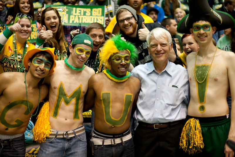 Former George Mason President, Dr. Alan Merten poses or photos with students during halftime of the George Mason Patriots vs James Madison Dukes men's basketball game at the Patriot Center on Tuesday, January 15, 2013. Photo by Craig Bisacre/Creative Services/George Mason University