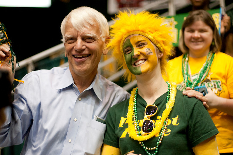 President Emeritus Alan Merten poses or photos with a student during halftime of the George Mason Patriots vs James Madison Dukes men's basketball game at the Patriot Center on Tuesday, January 15, 2013. Photo by Craig Bisacre/Creative Services/George Mason University