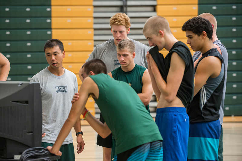 Fred Chao (L), head coach of the Men's Volleyball team, reviews film of the team's practice at the Recreation and Athletic Complex at Fairfax Campus. Photo by Alexis Glenn/Creative Services/George Mason University