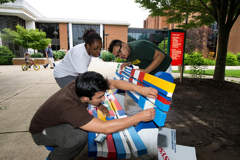 Students of the Hispanic Student Association paint a bench outside SUB 1 at Fairfax Campus. Photo by Alexis Glenn/Creative Services/George Mason University