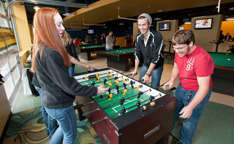Students play foozball at Corner Pocket in The Hub on Fairfax Campus.