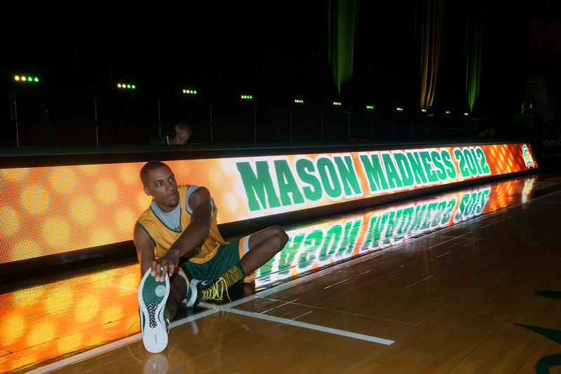 A basketball player stretches before Mason Madness at the Patriot Center. Photo by Alexis Glenn/Creative Services/George Mason University