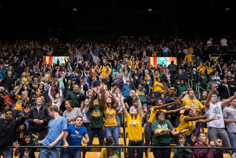 Students reach for t-shirts being tossed into the crowd at Mason Madness at the Patriot Center. Photo by Alexis Glenn/Creative Services/George Mason University