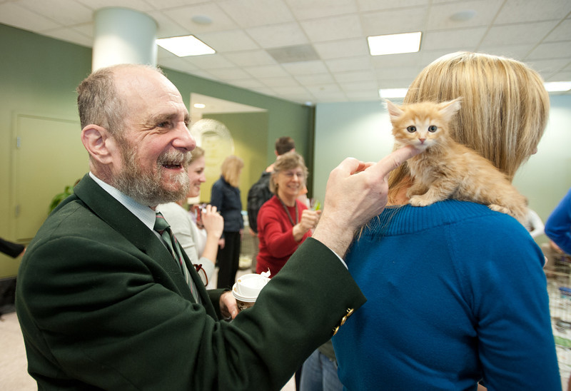 Law School Dean Daniel Polsby pets a kitten at the Law School's Puppy Day in the Robert A. Levy Atrium in Hazel Hall at George Mason University's Arlington Campus. The event, part of de-stress week, is hosted by A Forever-Home Rescue Foundation and Homeward Trails, two non-profit animal rescue groups. Photo by Alexis Glenn/Creative Services