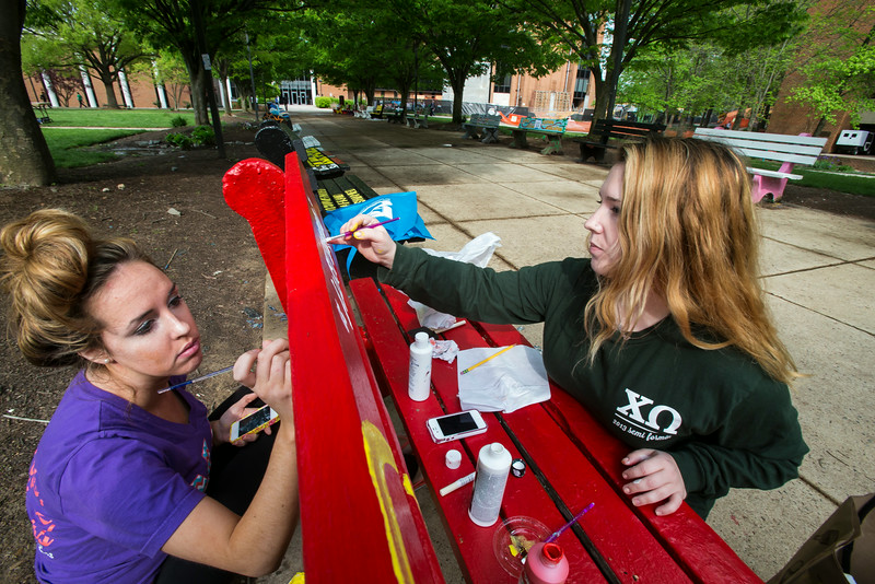 Chi Omega sorority sisters Mel Parr, left and Helen Ray, right, work on painting their sorority bench outside of Sub 1. Photo by Craig Bisacre/Creative Services/George Mason University