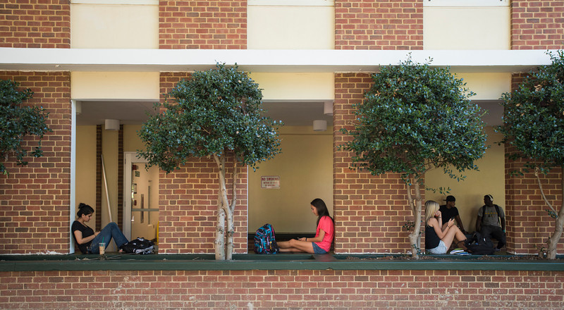 Students sit outside the East Building at Fairfax Campus. Photo by Alexis Glenn/Creative Services/George Mason University