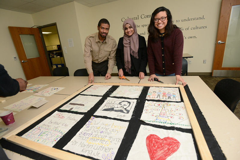 During the annual commemoration of Rev. Dr. Martin Lucther King, Jr. students attend a MLK quilt making session in the Office of Diversity, Inclusion and Multicultural Education (ODIME). Pictured left to right: Walter Parrish, Sidra Kalsoom and Veronica Ramos-Coreas. Photo by Evan Cantwell/Creative Services/George Mason University