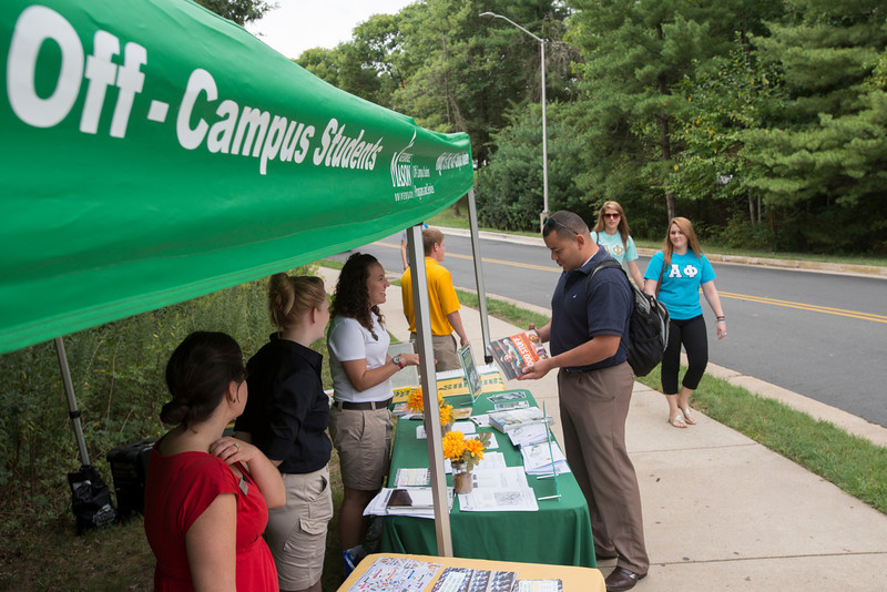 Off-Campus Student Programs and Services offer information and coffee to students near a parking lot on Fairfax campus. Photo by Alexis Glenn/Creative Services/George Mason University