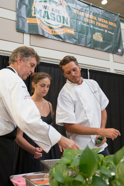 Celebrity Chef Spike Mendelson (R) and Sodexo Executive Chef Peter Schoebel give a cooking demonstration with a student at an Off-Campus Student Programs and Services event in the Johnson Center. Photo by Alexis Glenn/Creative Services/George Mason University
