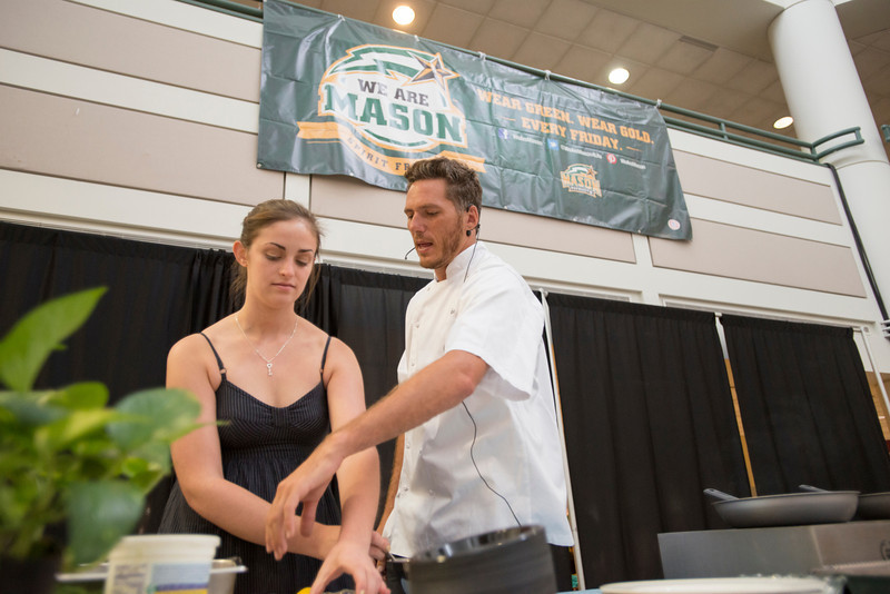 Celebrity Chef Spike Mendelson gives a cooking demonstration with a student at an Off-Campus Student Programs and Services event in the Johnson Center. Photo by Alexis Glenn/Creative Services/George Mason University