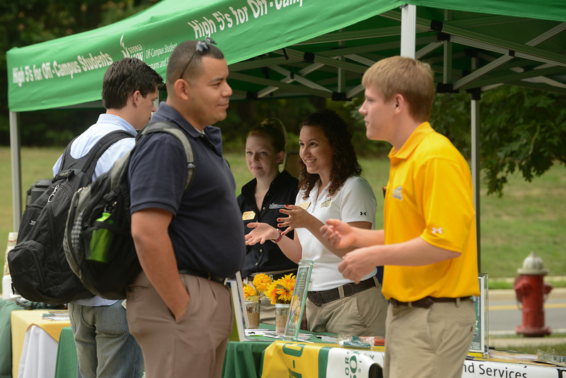 Off-Campus Student Programs and Services staff greet students with information, coffee and muffins. Photo by Evan Cantwell/Creative Services/George Mason University