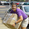 Sarah Schumacher, Assistant Director of Campus Ministry, lifts a heavy box during Move-In Day.