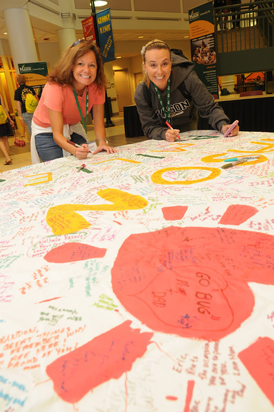 100713525 - Mason families sign a banner for students during Family Weekend 2010. Photo by Evan Cantwell.