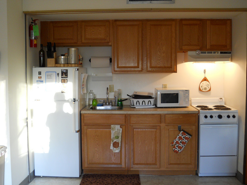 The kitchen has an efficiency refrigerator, oven, stove top, and sink. The microwave pictured here does not come with the apartment.