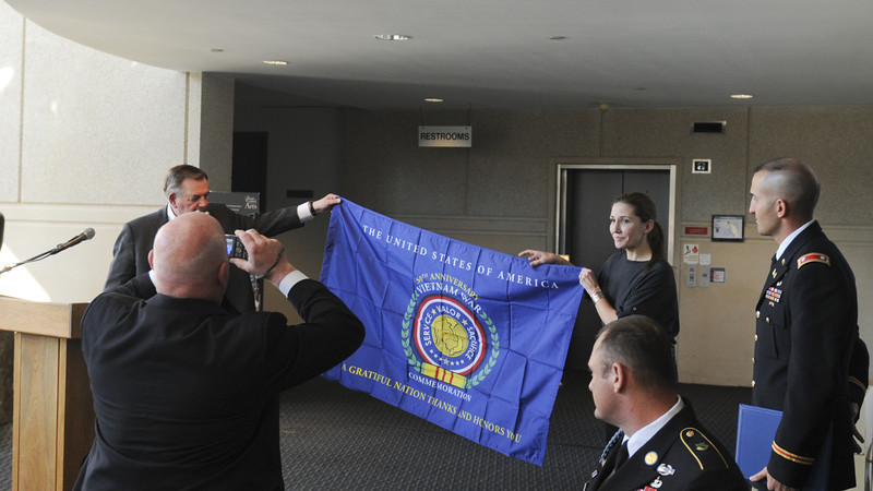 Retired Lt. Gen Kicklighter (L)presents the office of Military Services a Vietnam commemoration flag during the Veterans Day Luncheon on November 9, 2012.