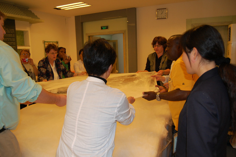 Tour members participating in making a silk comforter