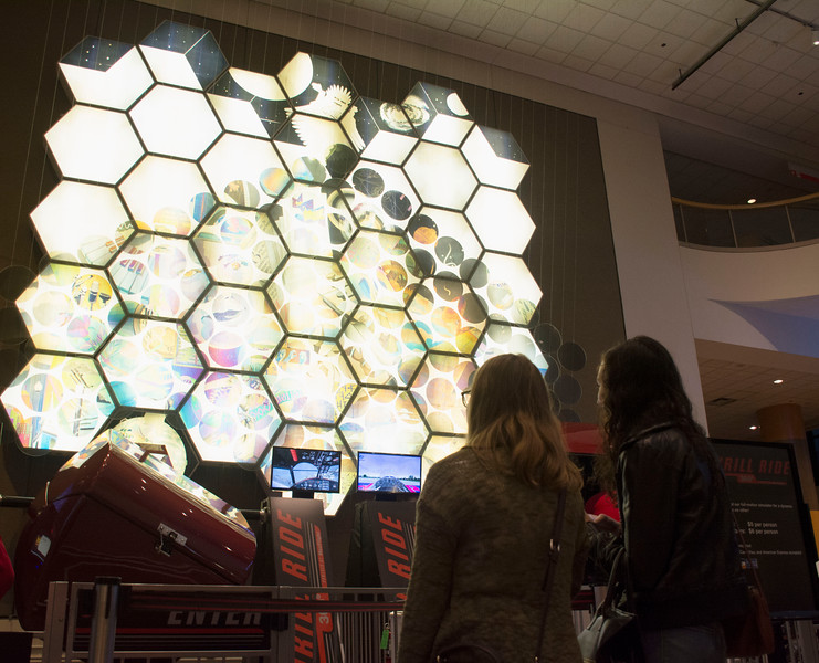"Two students view ""Human Connections,"" a polarized light art installation on display at the Museum of Science. The museum offered free admission to university students during its College Night event Friday evening."
