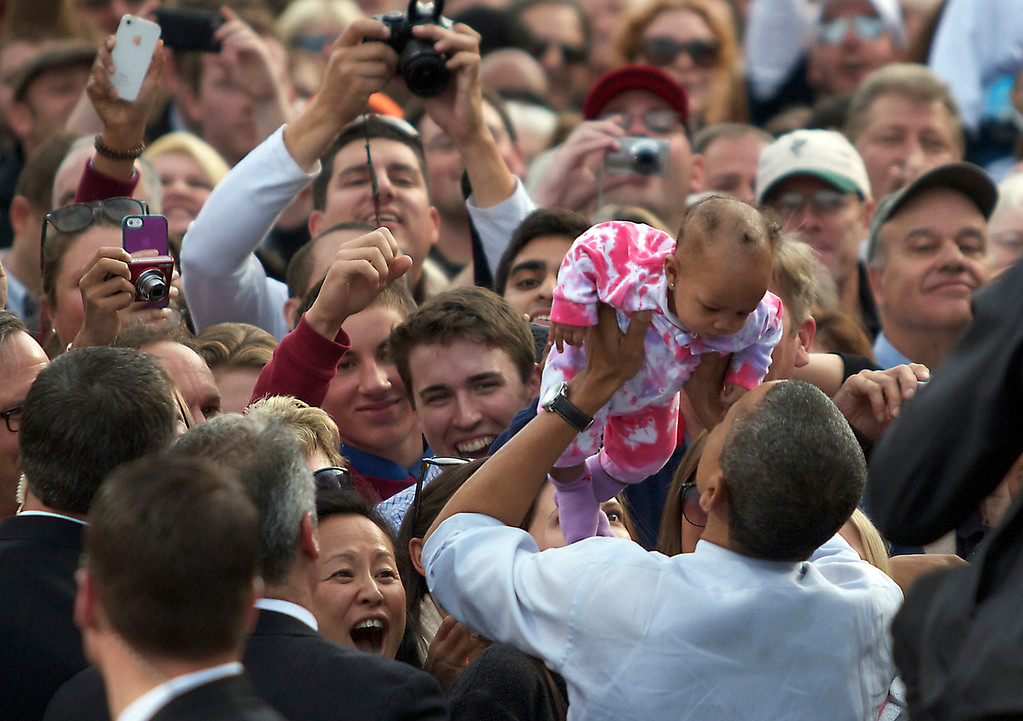 "October 27, 2012 -- President Barack Obama holds a supporter's baby following his speech at Elm Street Middle School in Nashua, New Hampshire during the ""Around the Clock for Barack: the 24 Hour Tour for the Middle Class"" campaign.  According to an Obama campaign source 8,500 people turned up to this event, the president's sixth appearance in the swing state in 2012, and the tenth since his presidency began."