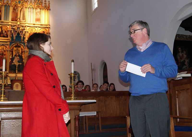 Fr. Morris of St. Mary's presents a check to Anna for her winning film.