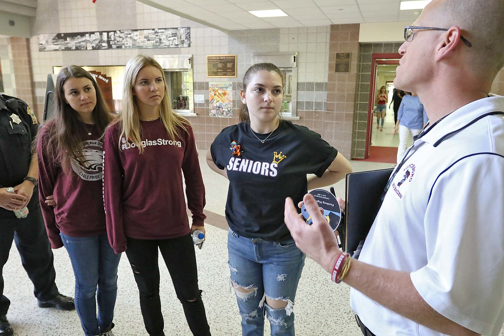 . Fitchburg High School Principal Jeremy Roche, on right, greets the three students from Stoneman Douglas High School in Parkland, Florida when they came to talk to students on Wednesday morning. From left is SDHS juniors Ma\'ayan Mizrahi, Madison Leal and Rebecca Schneid. SENTINEL & ENTERPRISE/JOHN LOVE