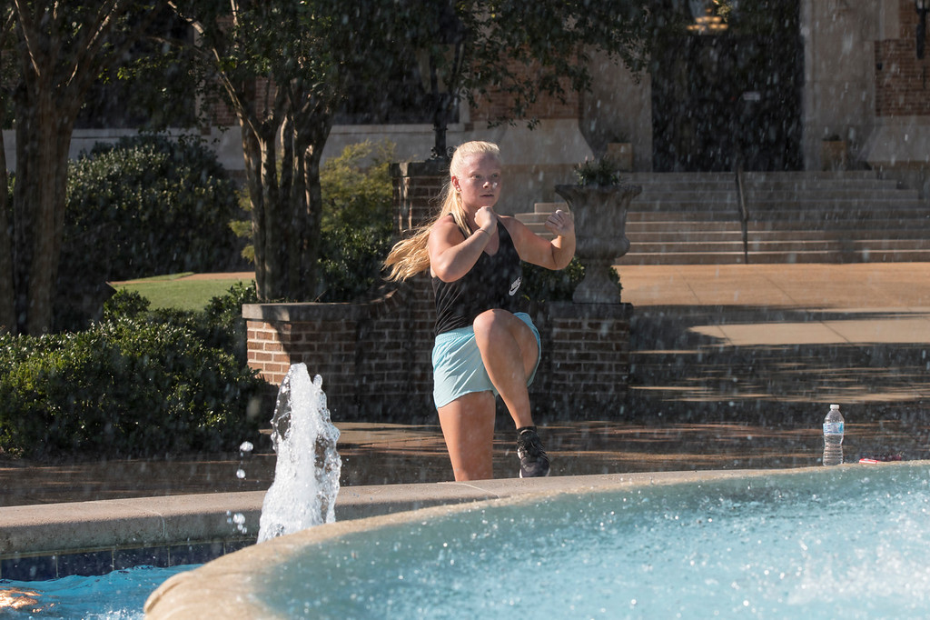 One of our majorettes exercisiing by the Harrison Fountain! Students around Campus