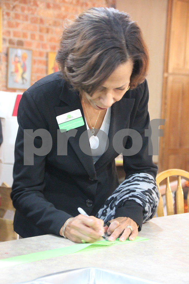 Pictured is: Clarice Thompson signing  the ribbon from the ribbon cutting ceremony.  Thursday, November 19, 2015, Studio Fusion had their ribbon cutting ceremony at Studio Fusion in Fort Dodge.