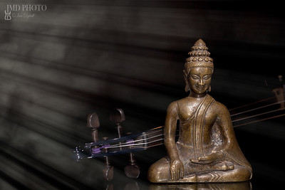 Spiritual, New Age, and religious music. Bronze buddha meditating with comtemporary violin in divine beam of light.