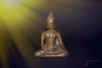 Buddhist meditation. Traditional bronze buddha meditating in rays of divine light. Zen buddhism and spiritual enlightenment or awakening.