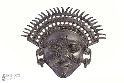 metal inca mask against white background